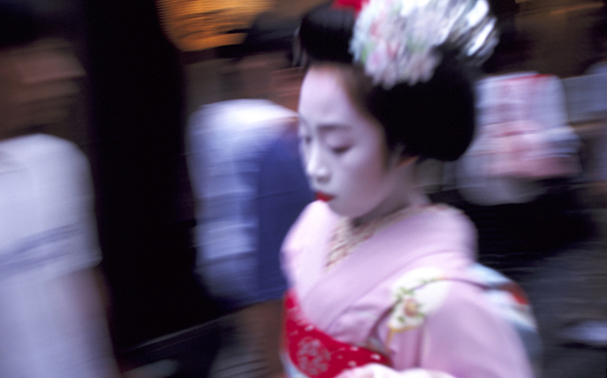 A maiko geisha in traditional make-up and kimono rushes to work through the narrow alley of Pontocho Street in Kyoto, Japan.